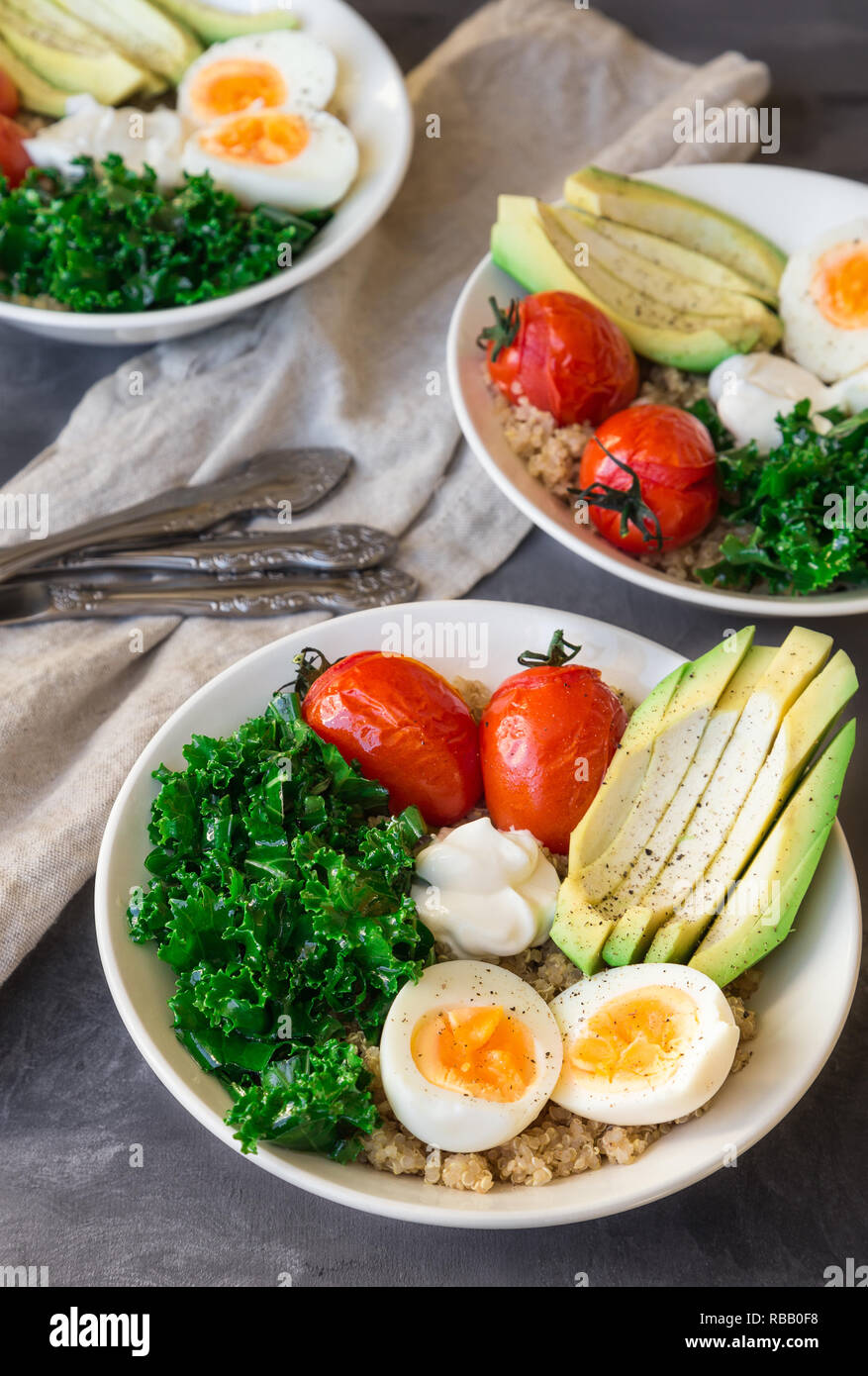 Quinoa buddha bowls with baked tomatoes, avocado, kale, boiled eggs and greek yogurt on gray concrete background. Healthy breakfast. Selective focus. - Stock Image