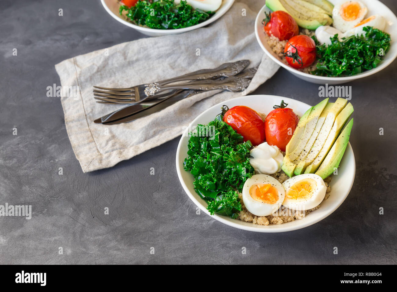 Quinoa buddha bowls with baked tomatoes, avocado, kale, boiled eggs and greek yogurt on gray concrete background. Healthy breakfast. - Stock Image