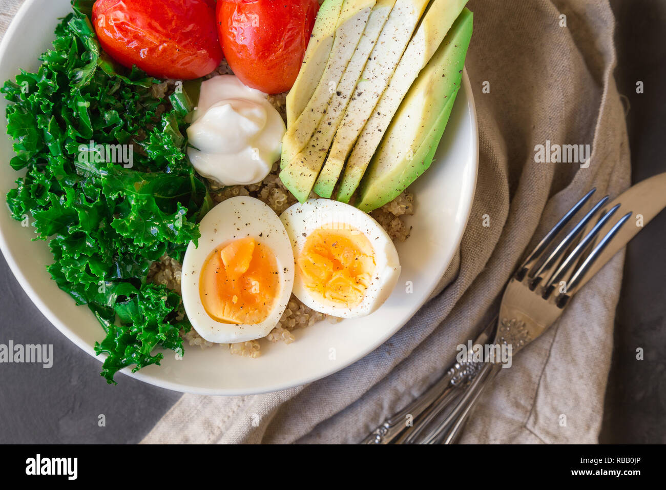 Quinoa buddha bowl with baked tomatoes, avocado, kale, boiled eggs and greek yogurt on gray concrete background. Healthy breakfast. Top view. - Stock Image