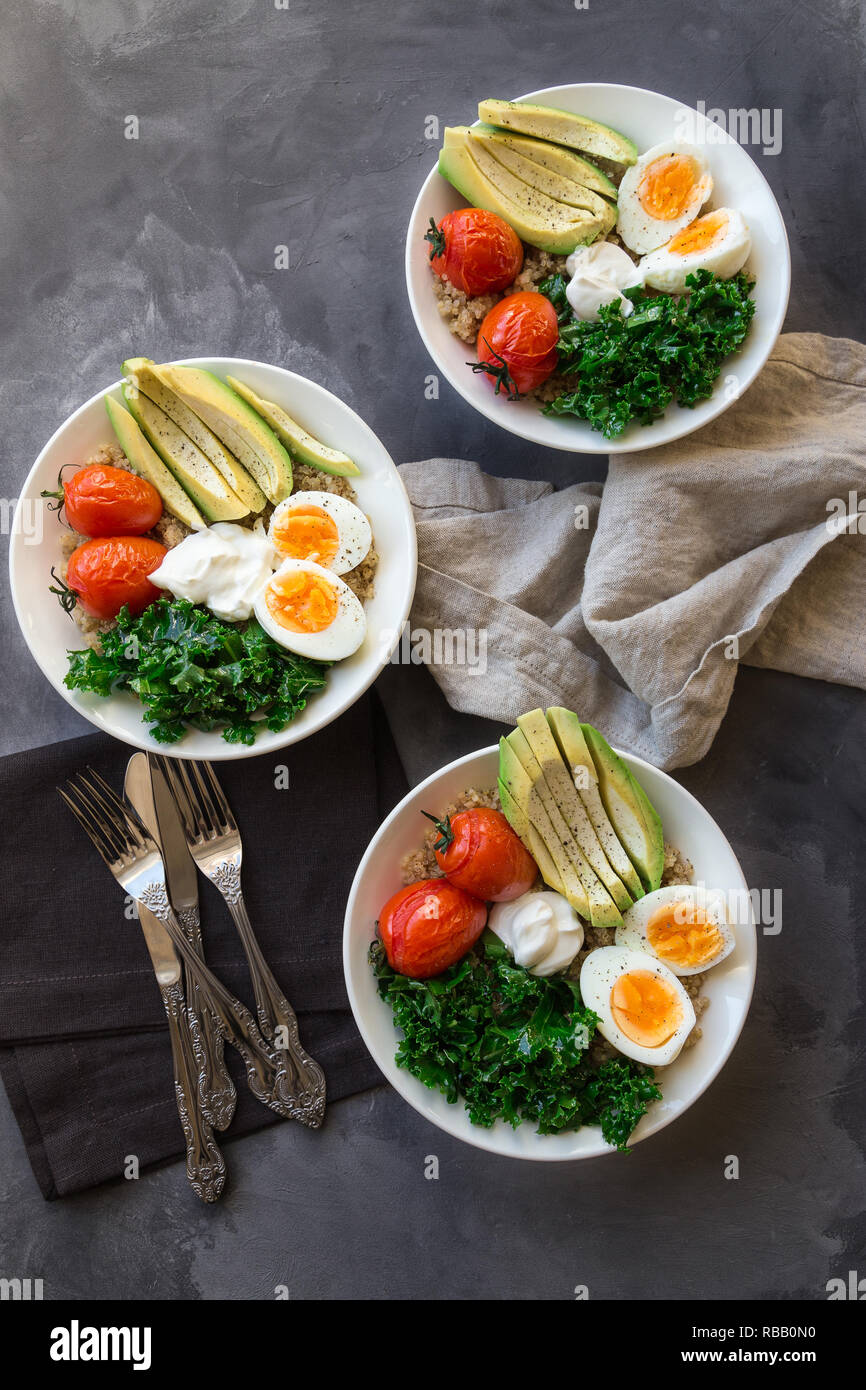 Quinoa buddha bowls with baked tomatoes, avocado, kale, boiled eggs and greek yogurt on gray concrete background. Healthy breakfast. Top view. - Stock Image