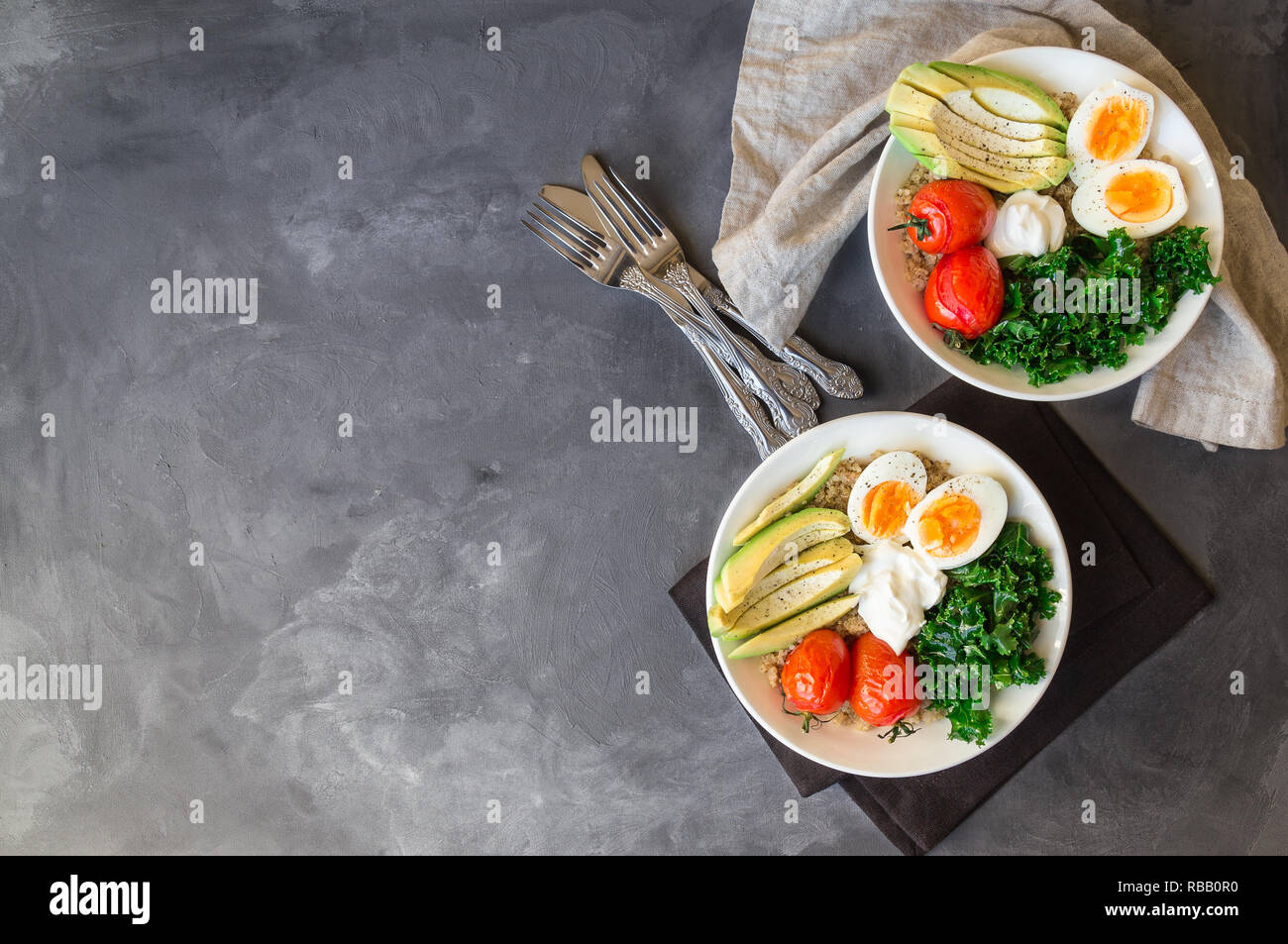 Quinoa buddha bowls with baked tomatoes, avocado, kale, boiled eggs and greek yogurt on gray concrete background. Healthy breakfast. Top view. Copy sp - Stock Image