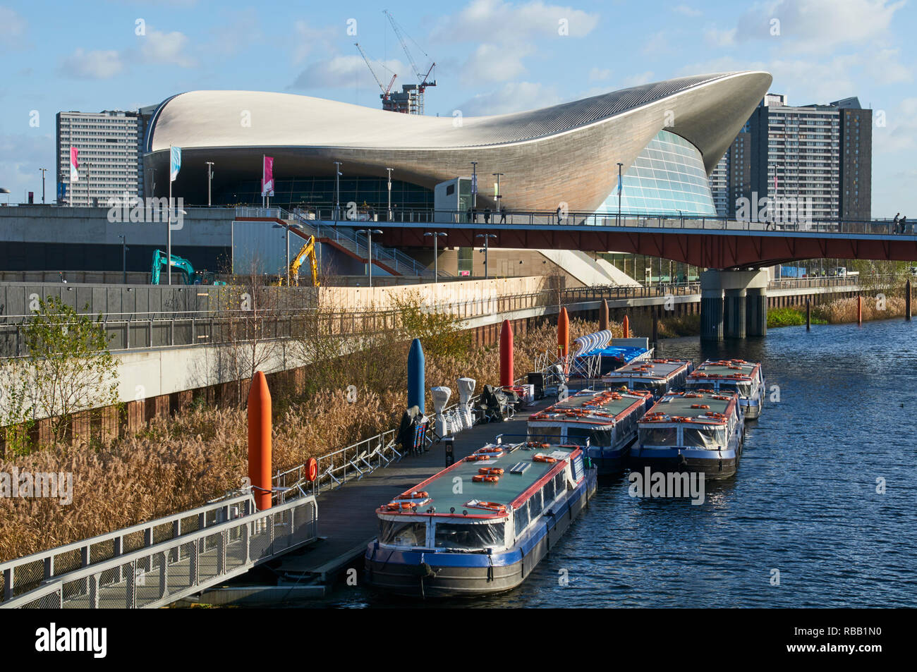 The London Aquatics Centre at Stratford, East London,  UK, with boats on the Waterworks River - Stock Image