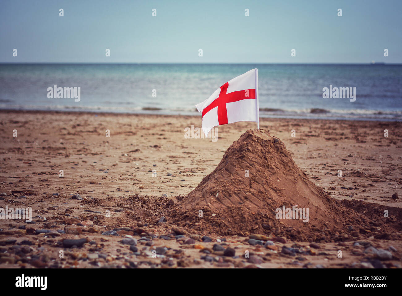 An English St George's Cross flag in a sandcastle on a British beach representing border and boundary control during illegal immigration issues in UK - Stock Image