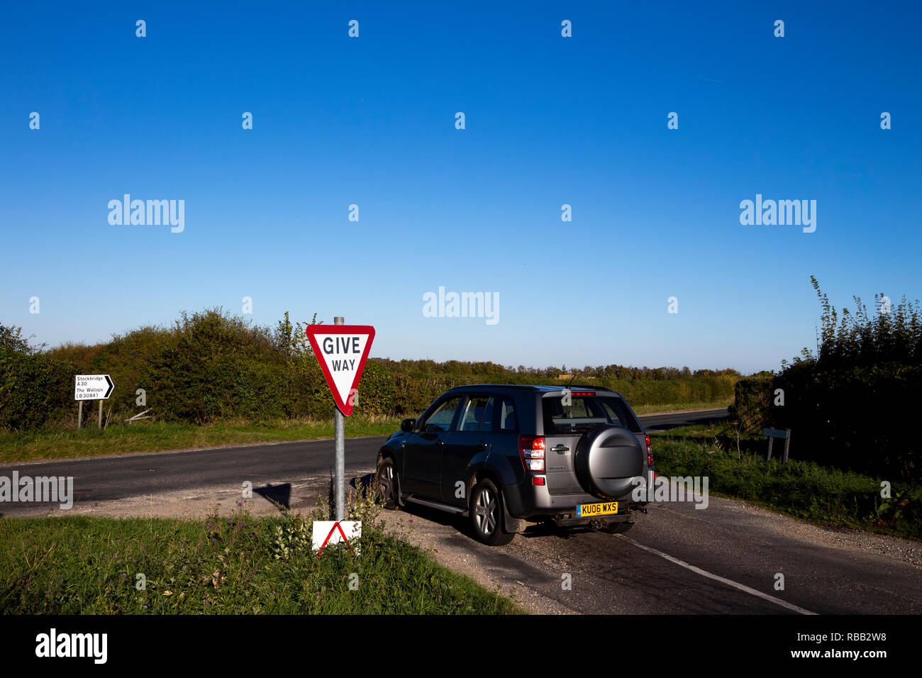 give way road sign on country lane joining main highway junction in rural Hampshire - Stock Image