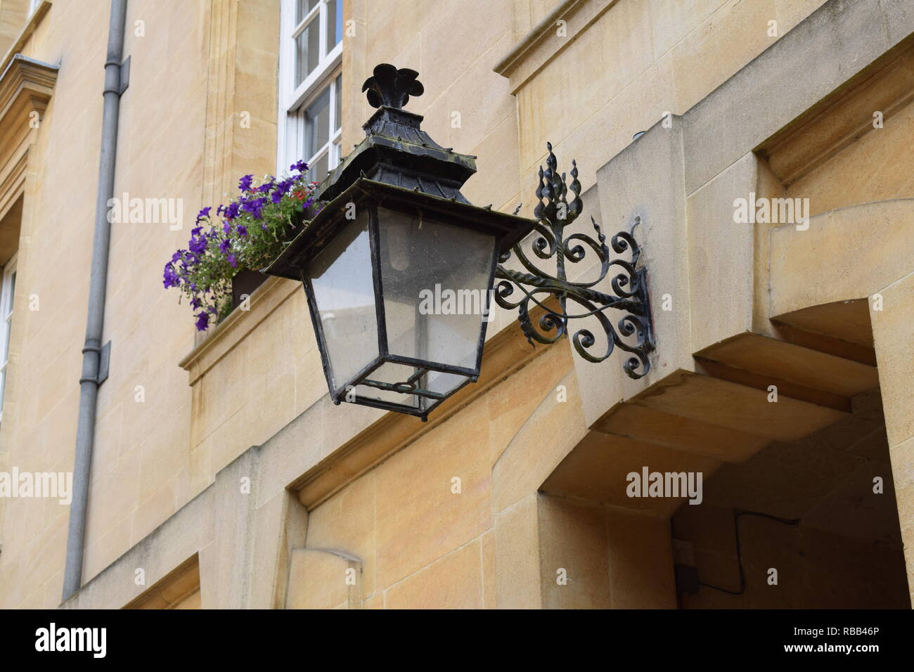 Lamp on the wall of Corpus Christi College Oxford - Stock Image