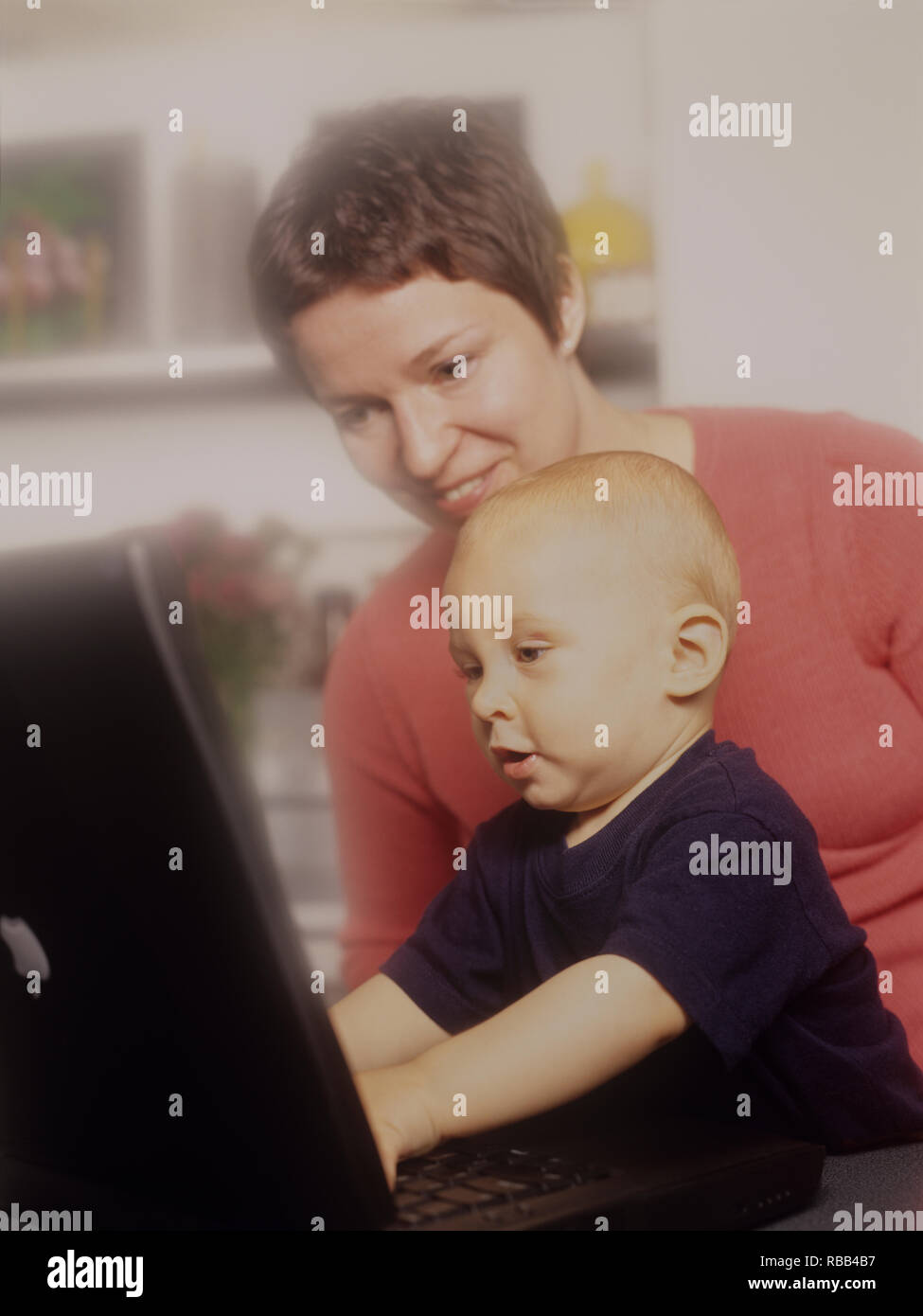 Mother and toddler son on a laptop computer enjoying screen time together - Stock Image