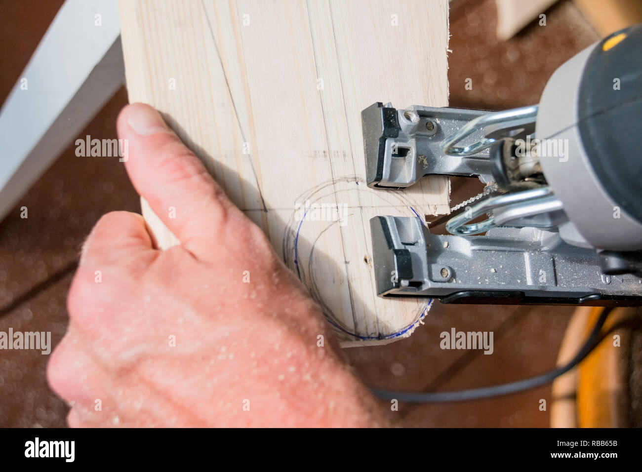 young man carpenter builder working with electric jigsaw and wood.hobby concept.DIY acronym cut out in OSB panel with electric jigsaw.Woodworker cutting a piece of wood - Stock Image