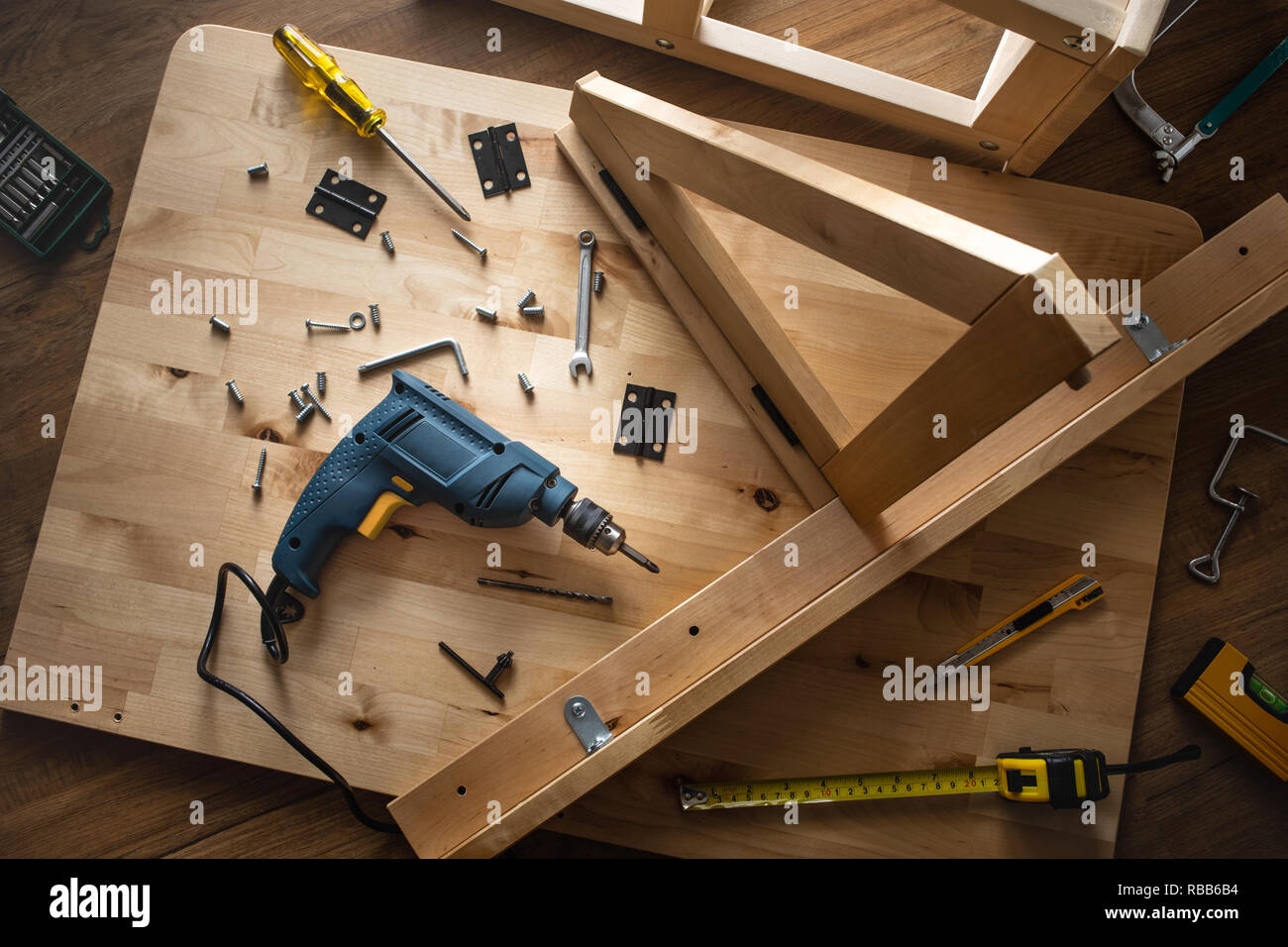 Top view of drill tool and another equipment on wood table furniture.assembly, improvement or repairing home interior concepts ideas - Stock Image