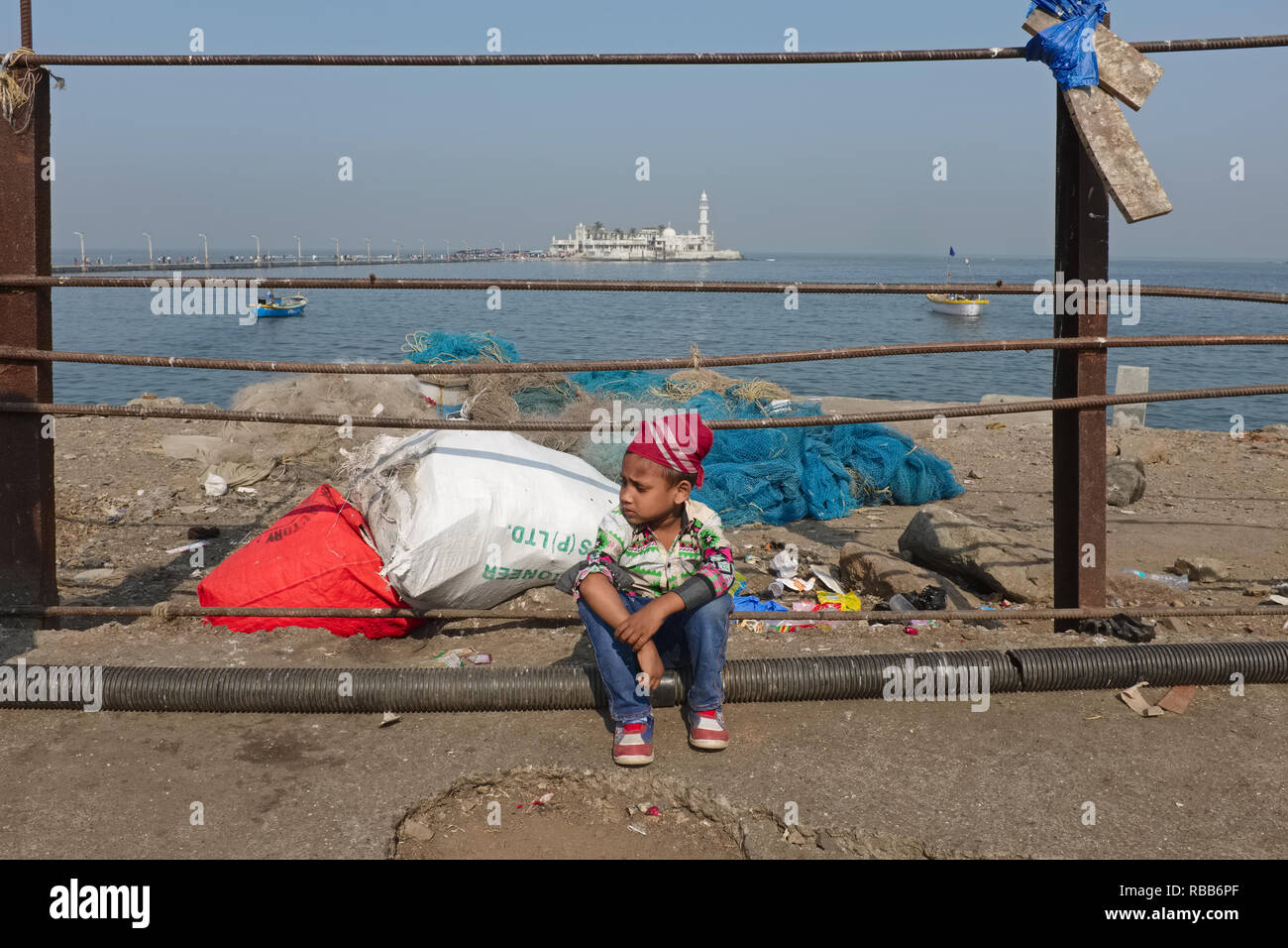 A young Muslim boy sits by Worli Bay in Mumbai, India, in the background Haji Ali Dargah and Mosque, the city's most revered Muslim place of worship - Stock Image