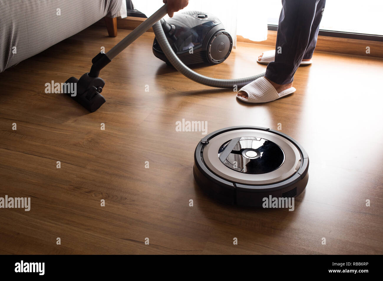 Robot vacuum cleaner with people mop the floor.Smart life concepts ideas - Stock Image