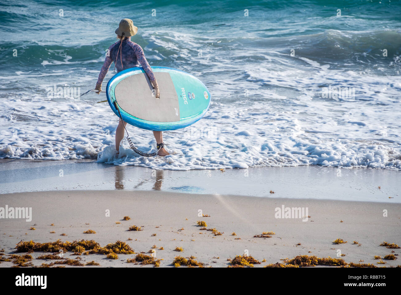 Female stand-up paddle boarder entering the ocean at Palm Beach, Florida. - Stock Image