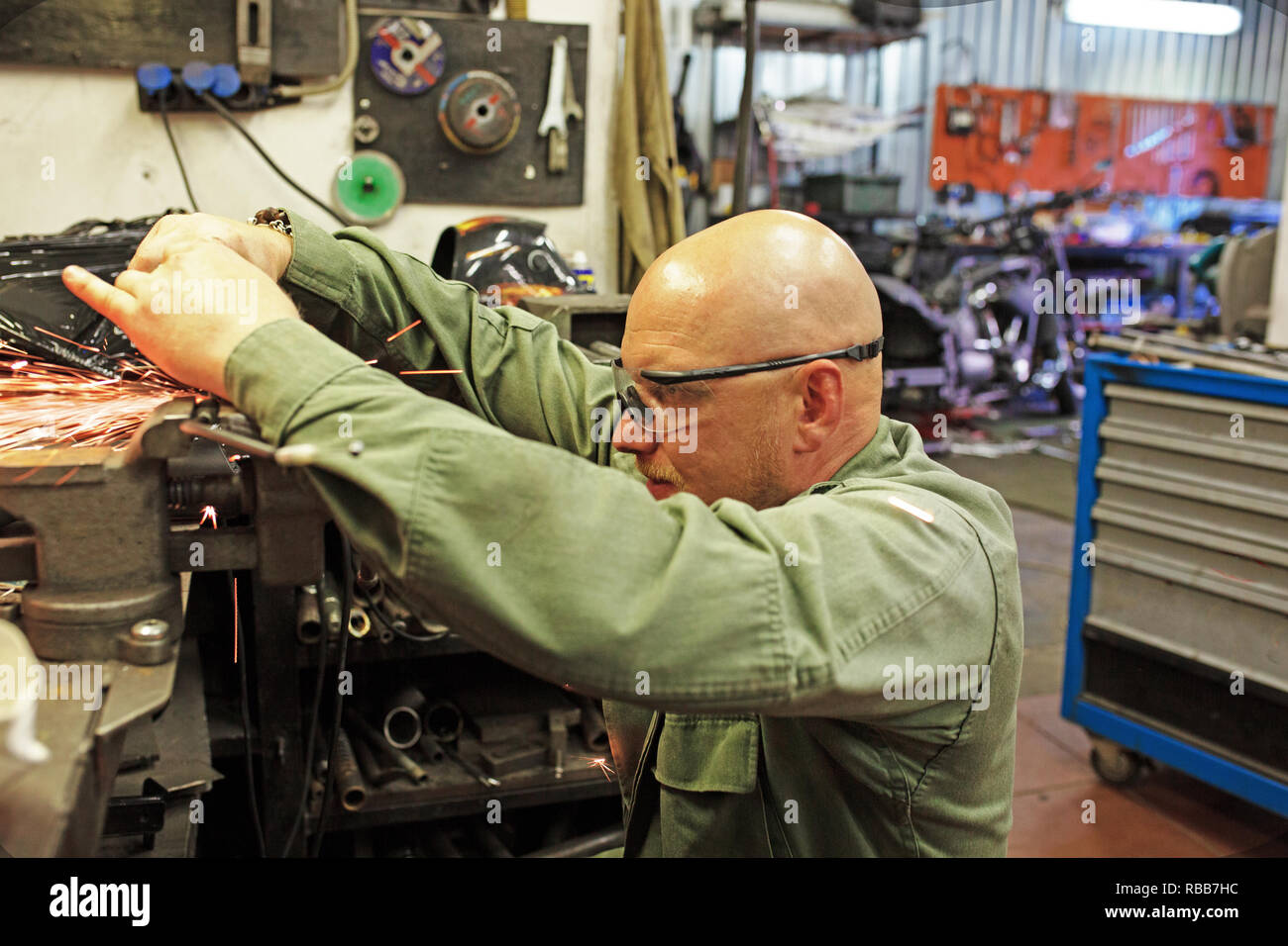 Heavy industry worker cutting steel with angle grinder at car service. - Stock Image