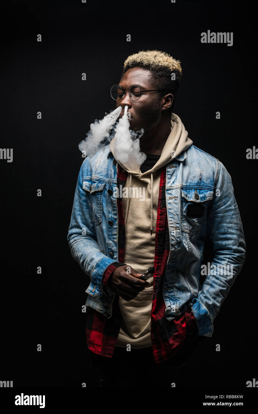 Portrait of african man it smoking an e-cigarette isolated on dark background. - Stock Image