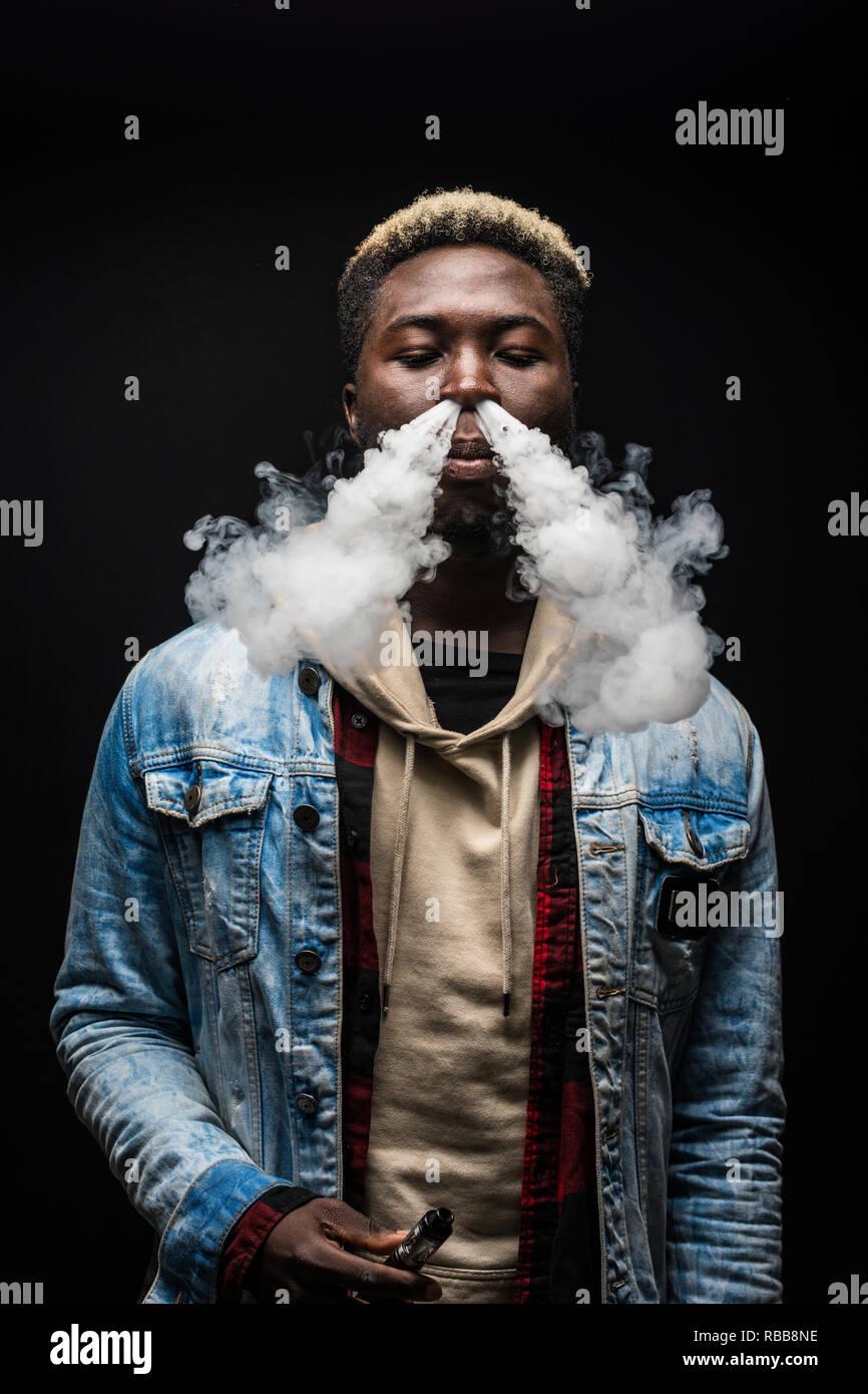 Young african man smoke vape isolated on dark background - Stock Image