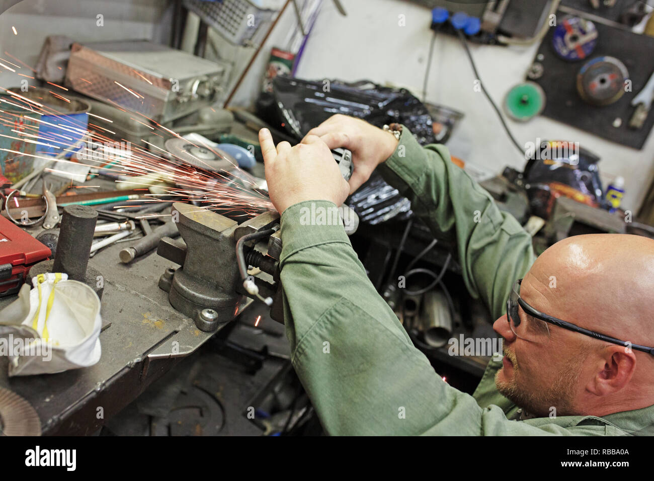 Heavy industry worker cutting steel with angle grinder at car service - Stock Image