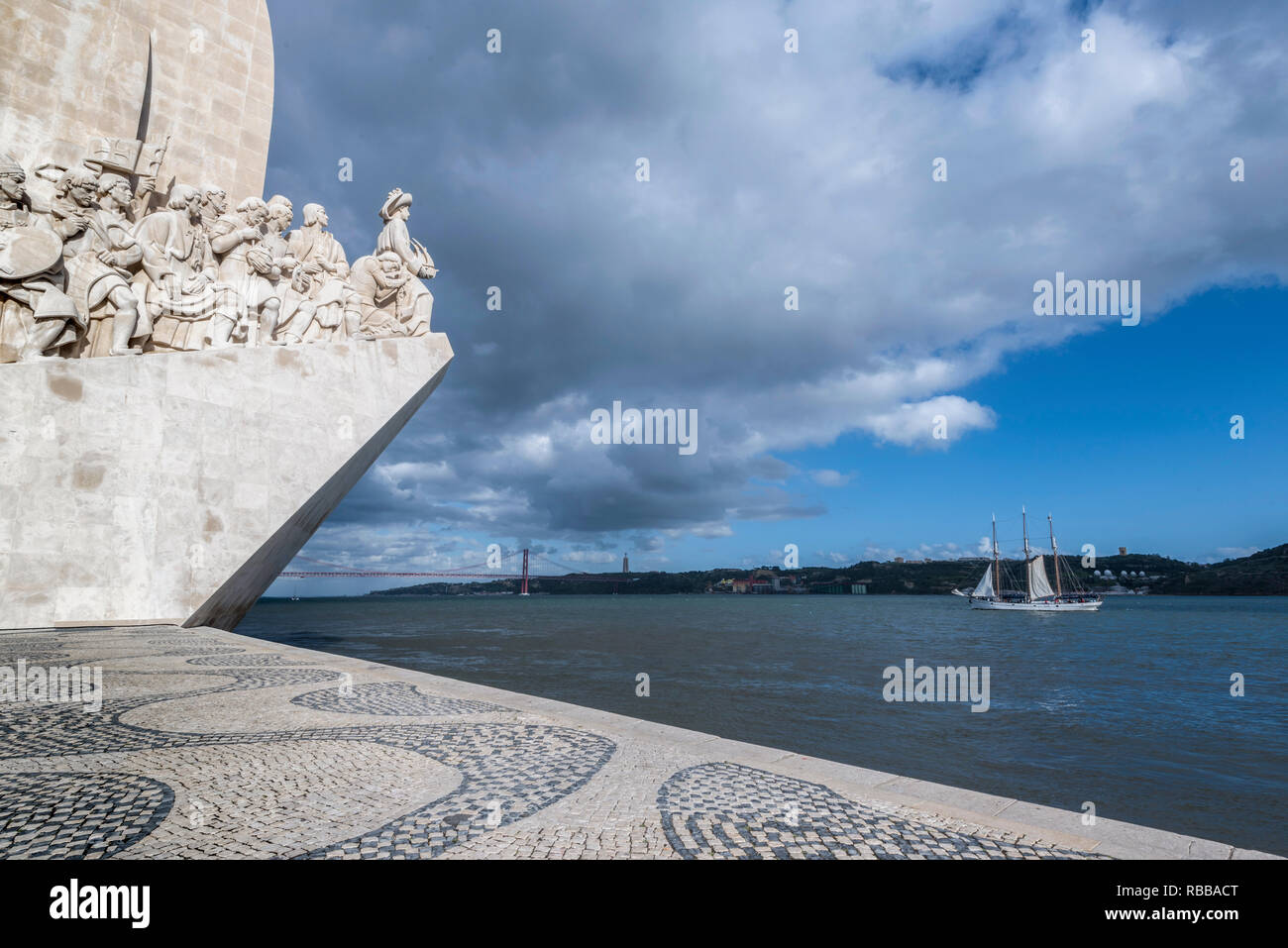 Glimpse of the monument to the discoveries and bridge 25 April on the river Tagus in Lisbon - Stock Image
