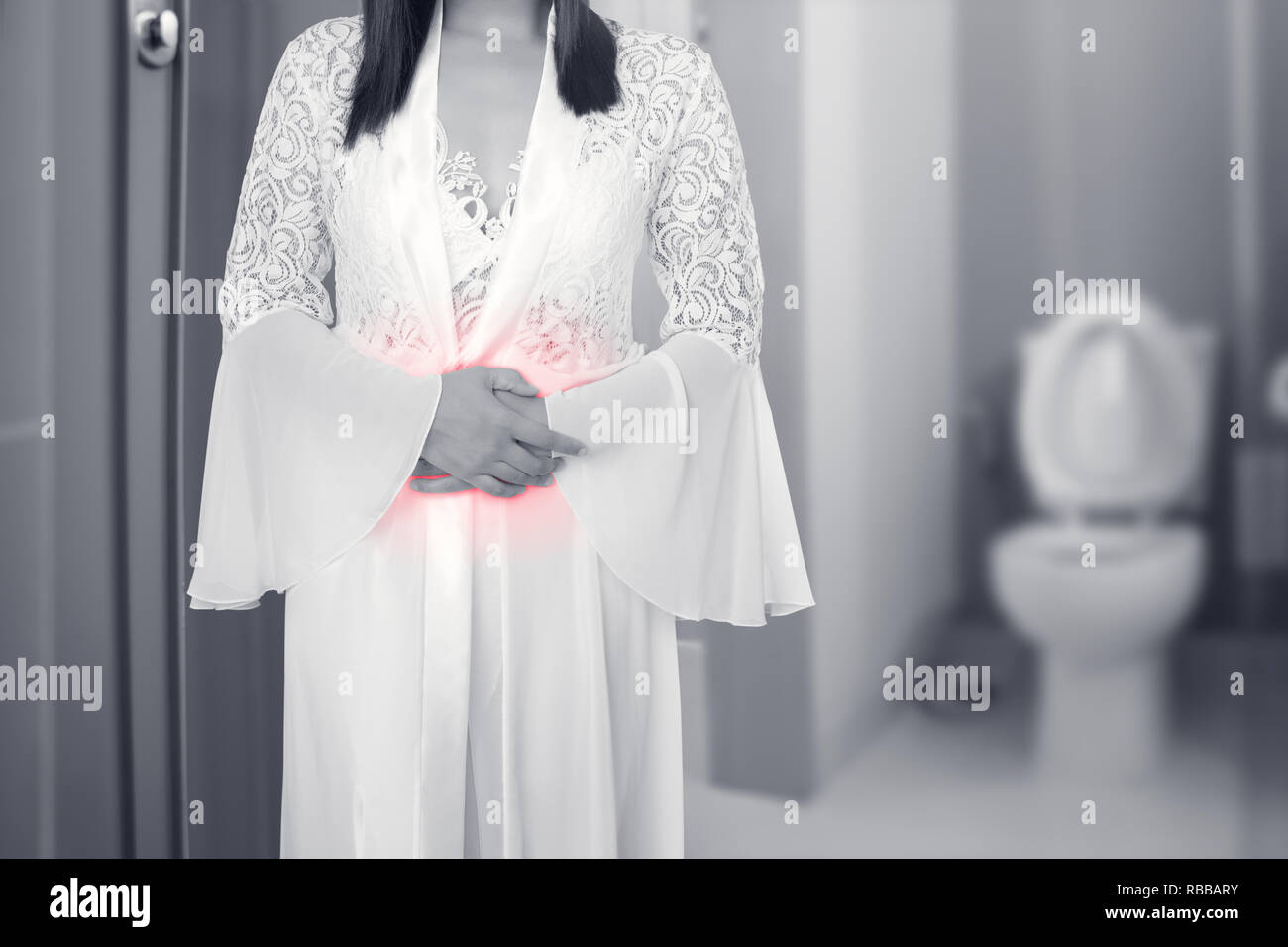 Woman in long white silky nightgown and lace robe touching belly painful suffering from stomachache causes of menstruation, Female in lace sleepwear w - Stock Image