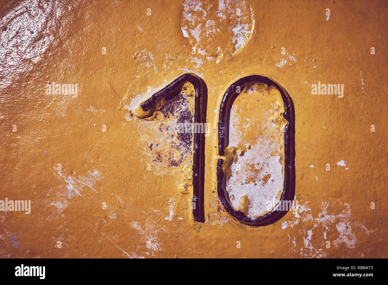 Number ten on yellow painted steel background, color toning applied. - Stock Image