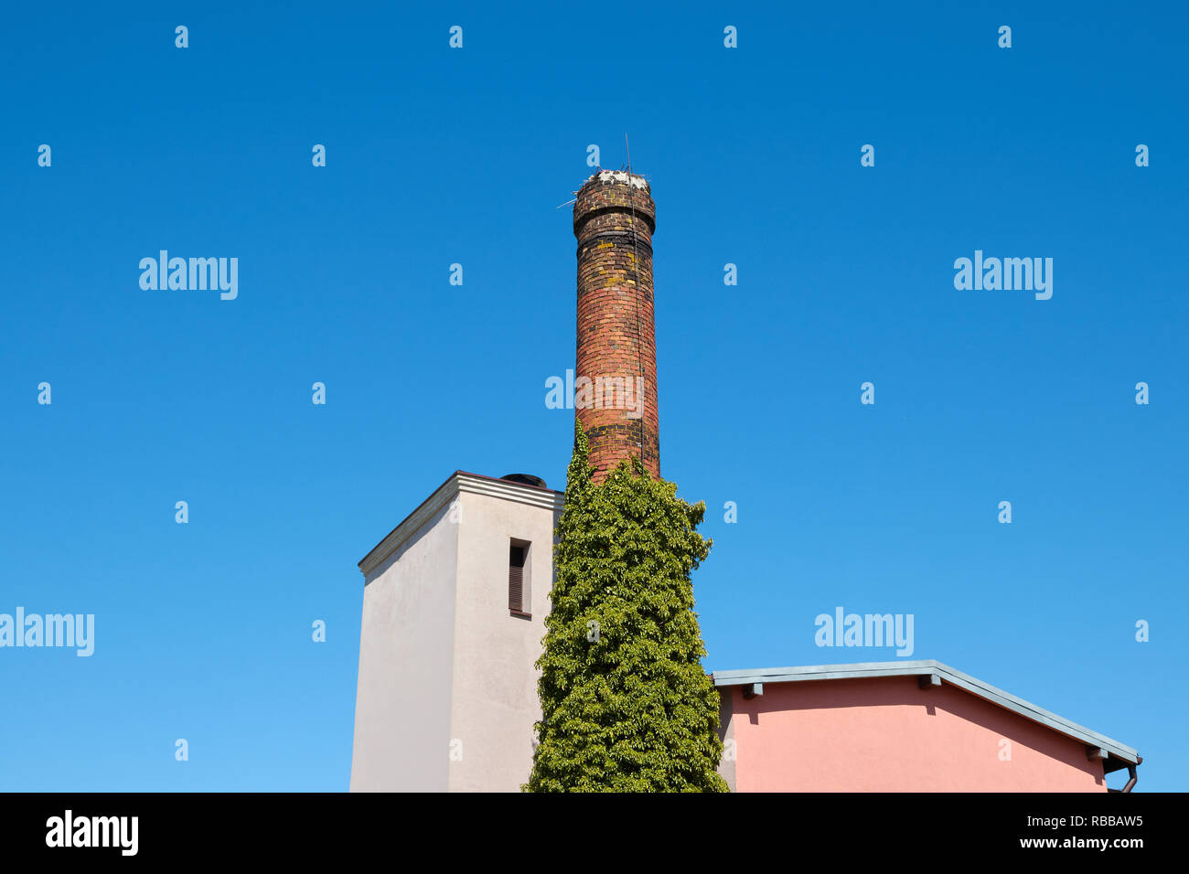 Old brick chimney against the blue cloudless sky. - Stock Image