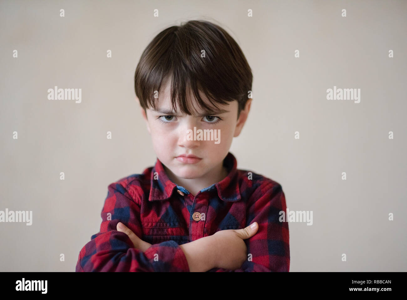 portrait of cute small angry upset caucasian kid in plaid shirt - Stock Image