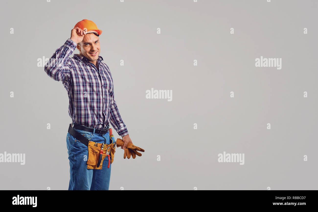 Smiling adult constructor in hardhat and greeting - Stock Image