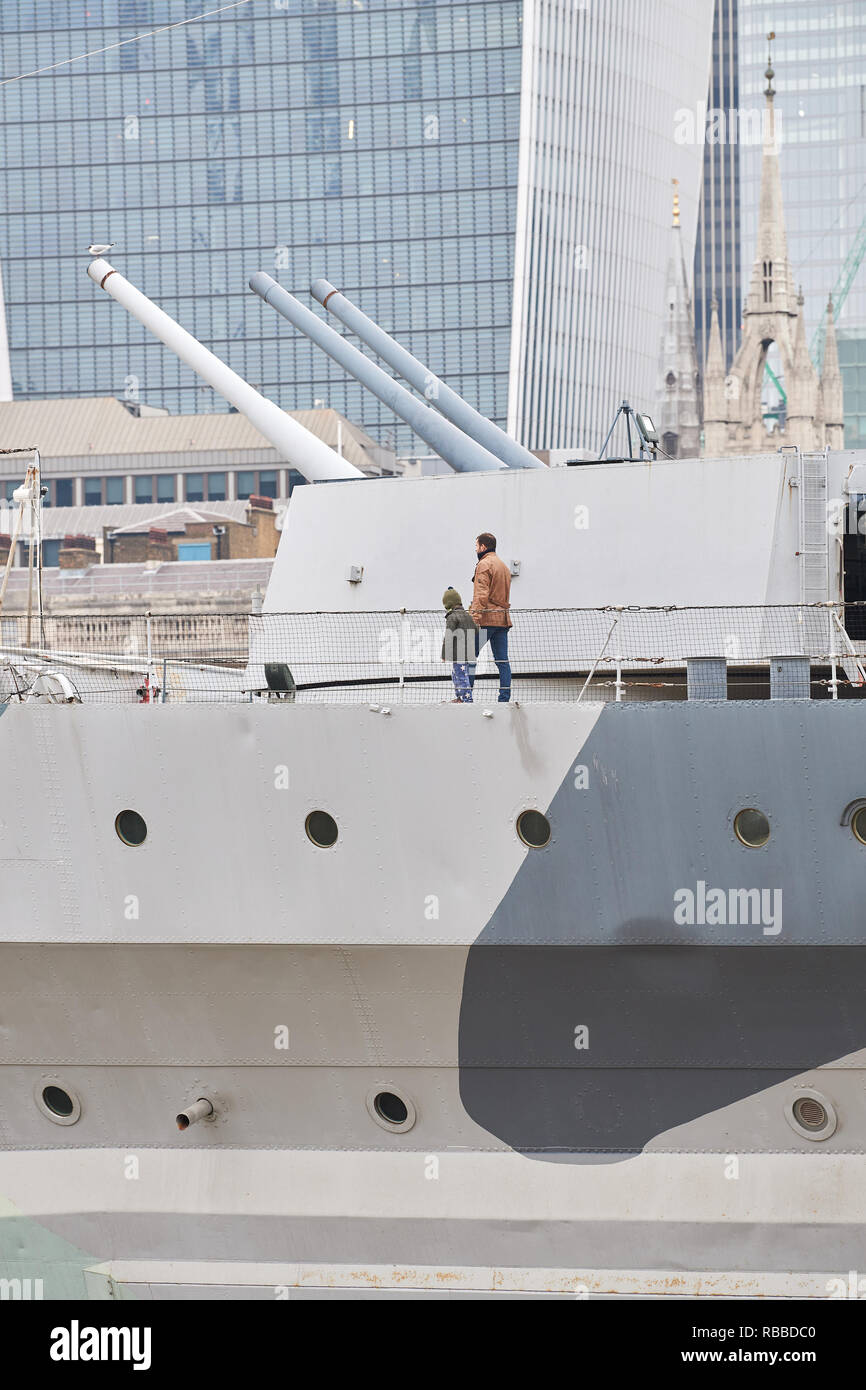 A man and his son pass the big guns on the warship HMS Belfast, a world war II cruiser ship now anchored on the river Thames in the city of London nea - Stock Image
