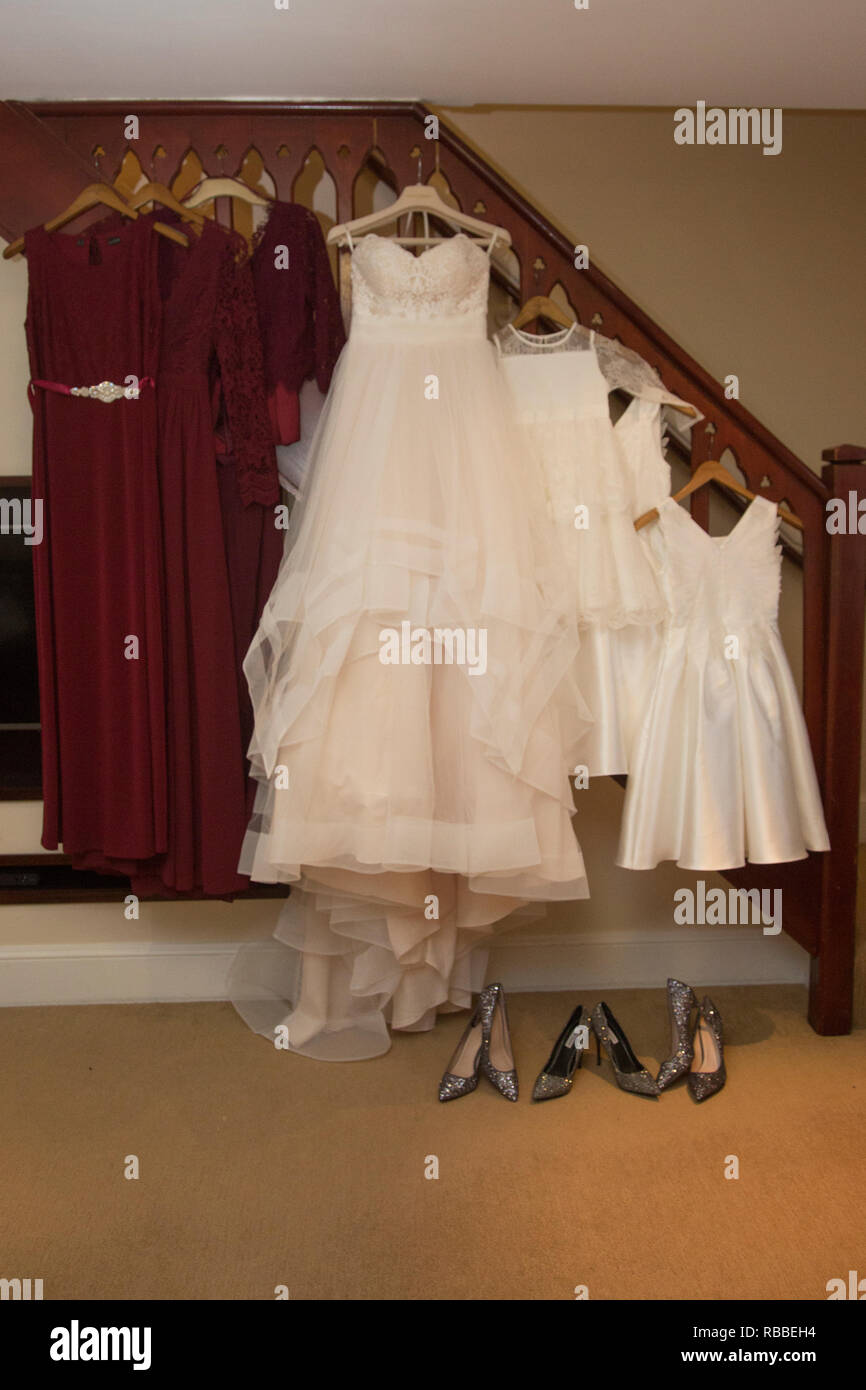 Brides wedding dress and red bridesmaids dresses hanging up waiting to be worn on the wedding day Stock Photo