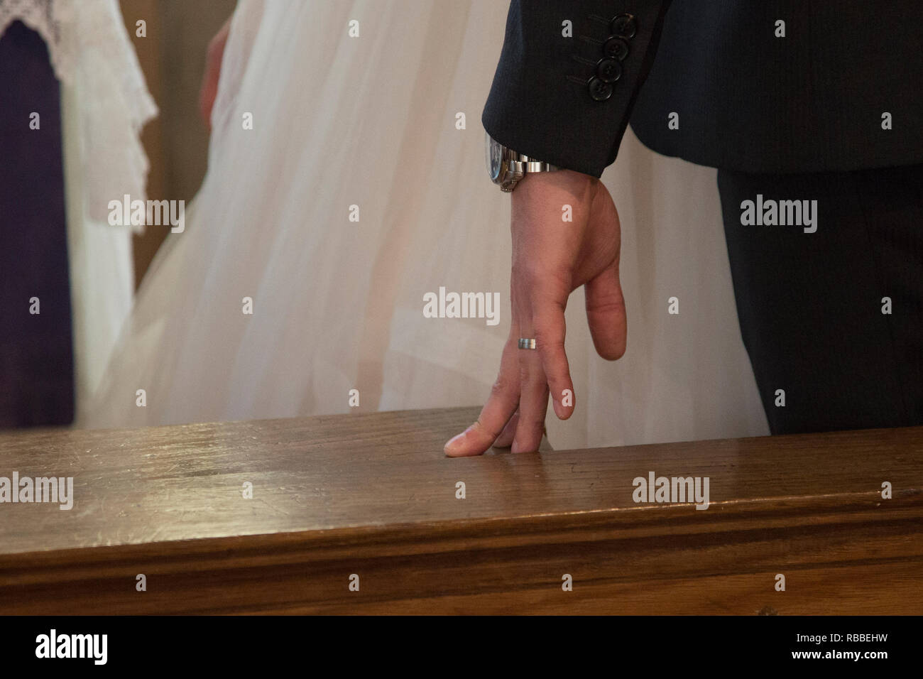 Close up of the grooms hand whilst waiting to sign the register, wedding ring is on his finger. - Stock Image