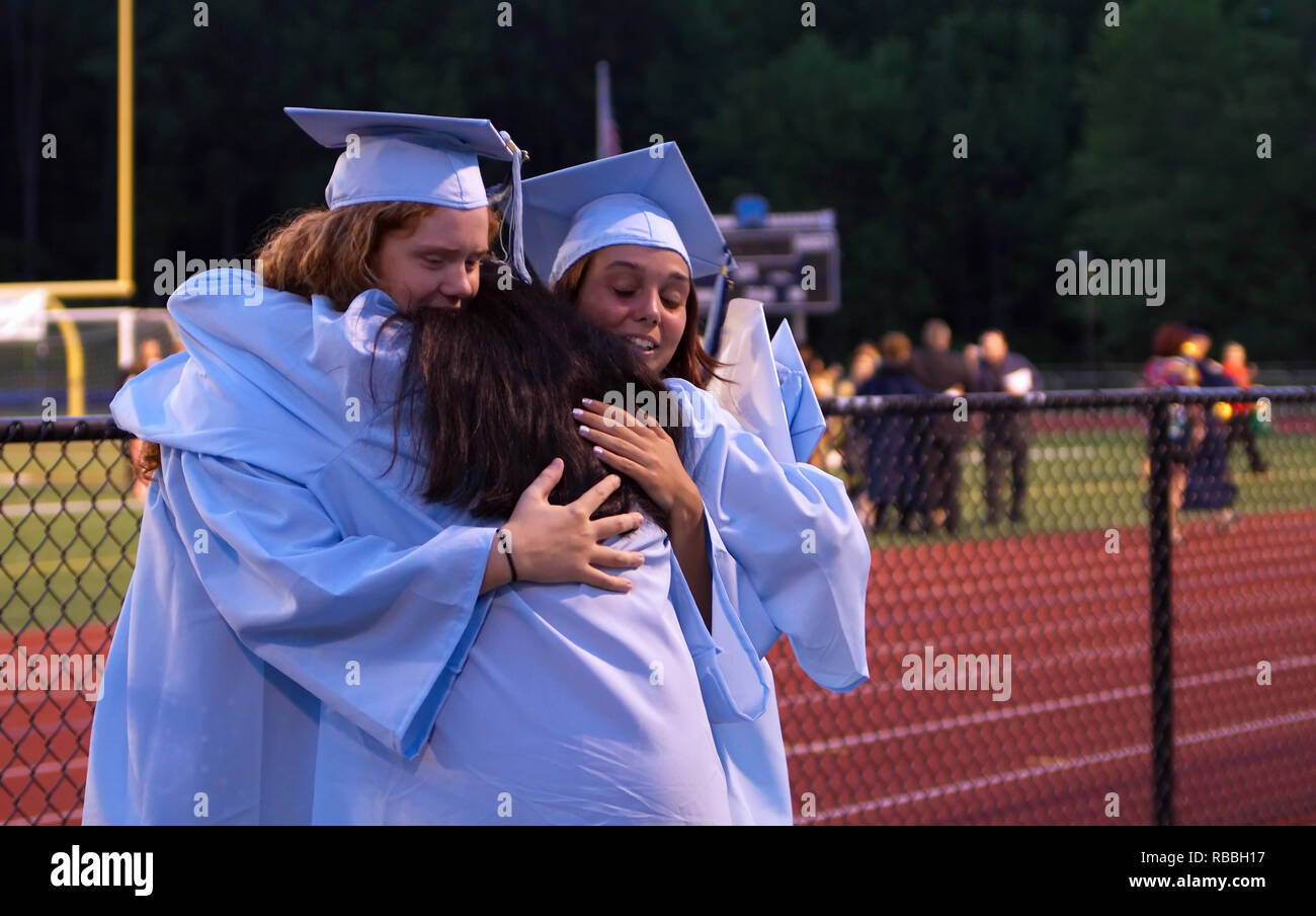 The sad and happy hug of the senior class as they head off to greater challenges in life. - Stock Image