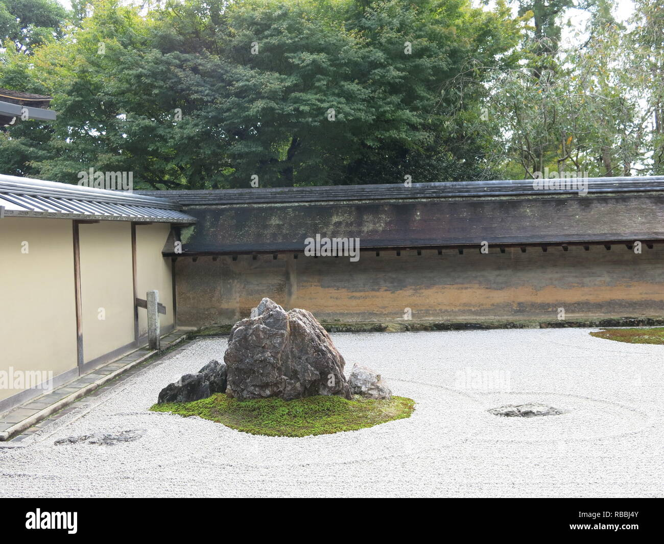 The famous dry rock garden at Ryoan-ji Zen Buddhist temple in Kyoto; featuring carefully placed boulders, moss and raked gravel against a clay wall - Stock Image