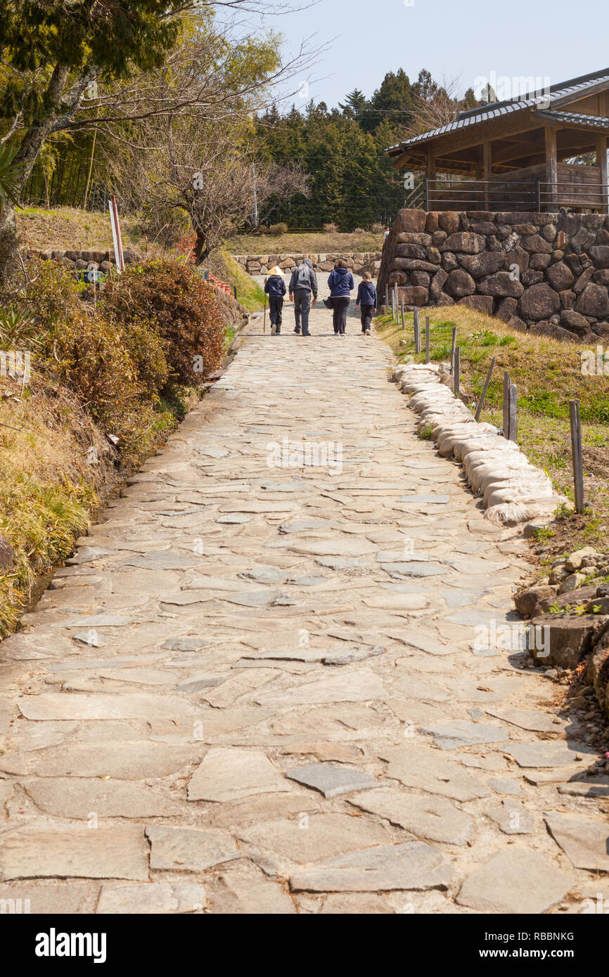 4 people walking up japanese path in the country in spring - Stock Image
