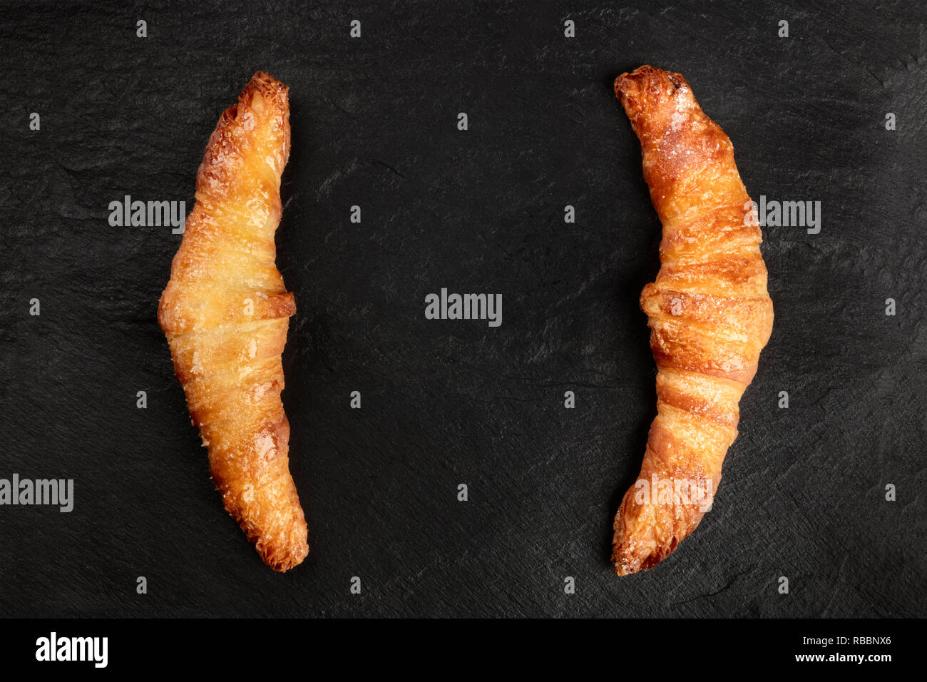 Two croissants on a black background, shot from above, forming brackets for copy space - Stock Image