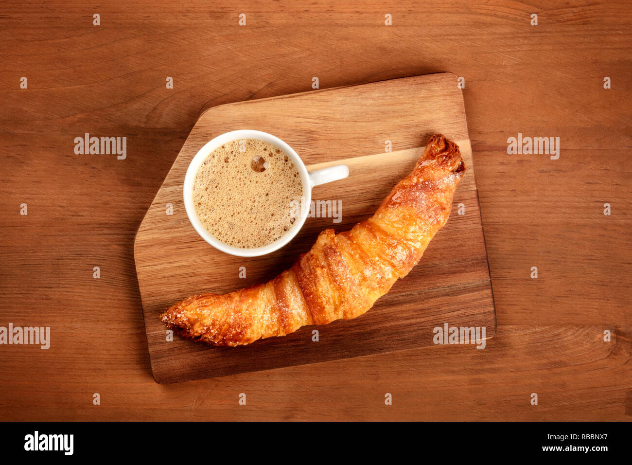 A photo of a croissant with a cup of coffee on a wooden tray, shot from above on a dark rustic background with copy space - Stock Image