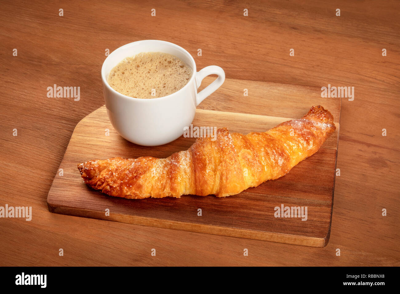 A photo of a croissant on a dark rustic wooden background with coffee and a place for text - Stock Image