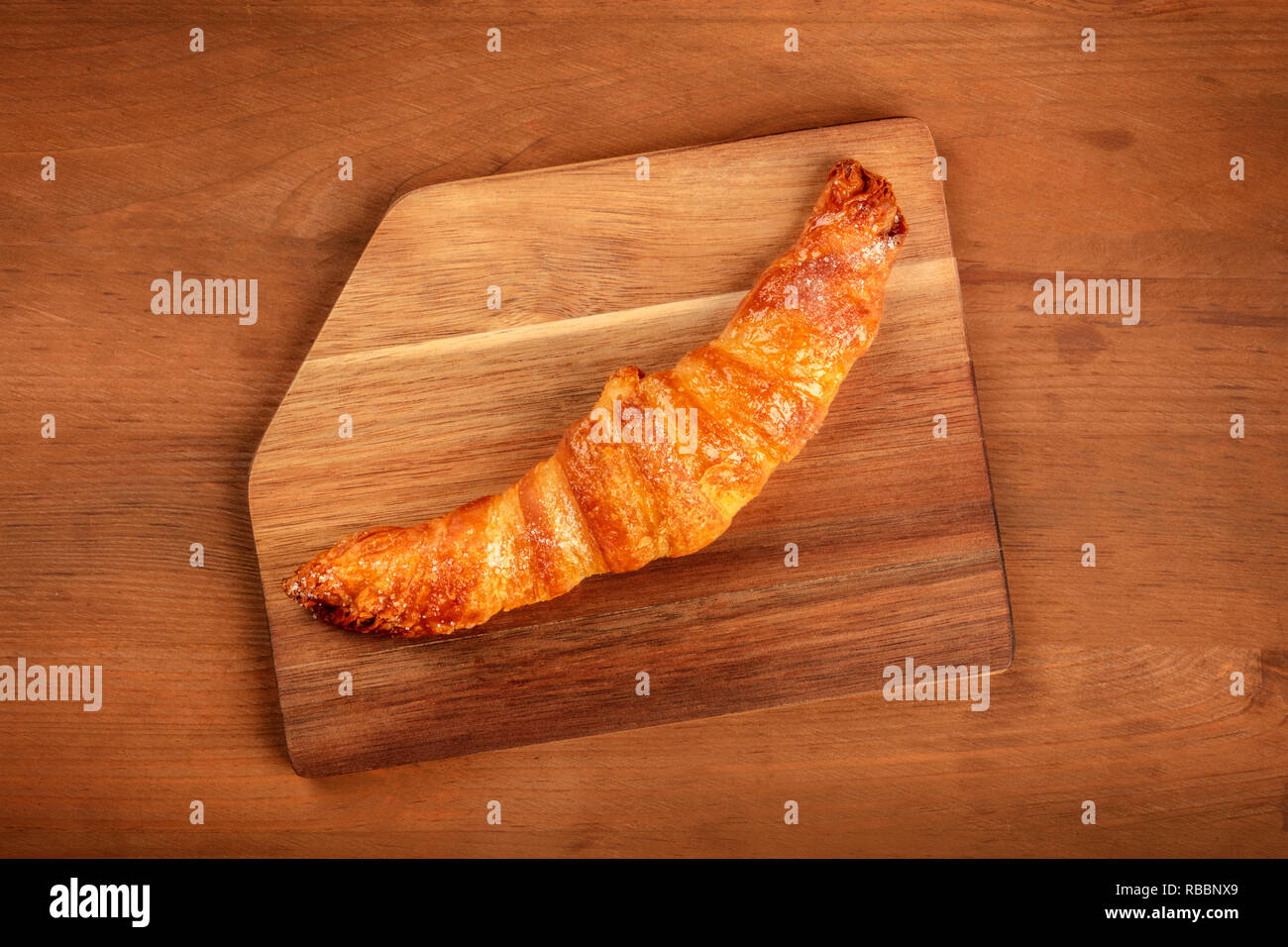 A photo of a croissant on a dark rustic wooden background, shot from the top with copy space - Stock Image