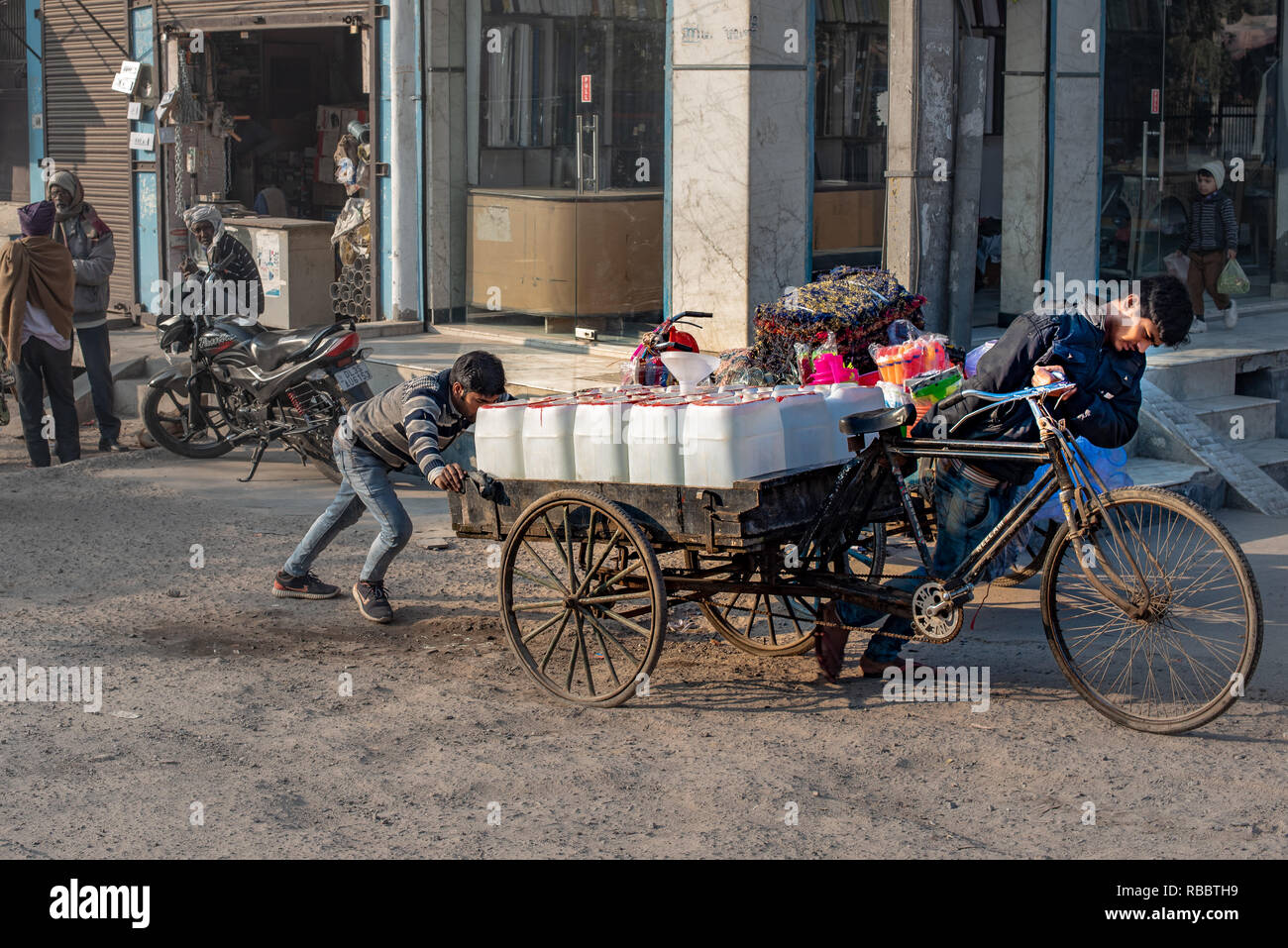 Sharing the burden: Supplying vital drinking water to Khadar's residents in an arduous job (in JJ Colony, Madanpur Khadar, New Delhi) - Stock Image