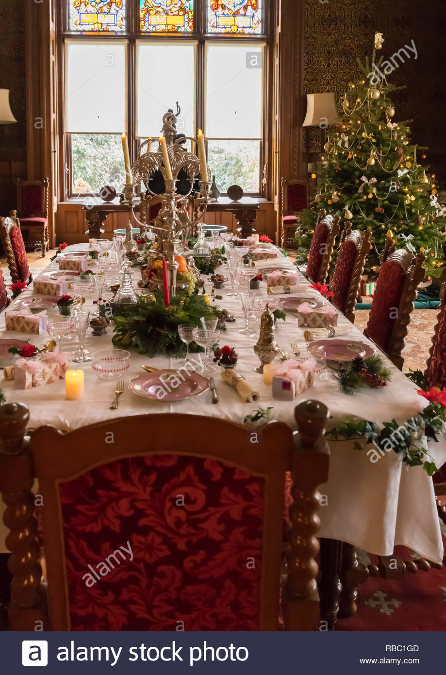 A grand Christmas table laid with a candlestick, decorations and a tree inside Charlecote Park. - Stock Image