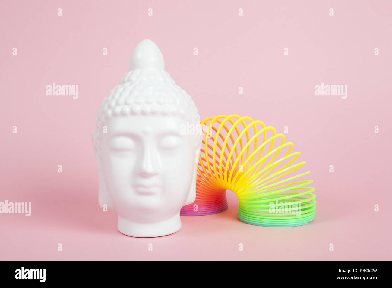 a white porcelain bouddha head placed near rainbow spring on a pink and vibrant background. Minimum color still life - Stock Image