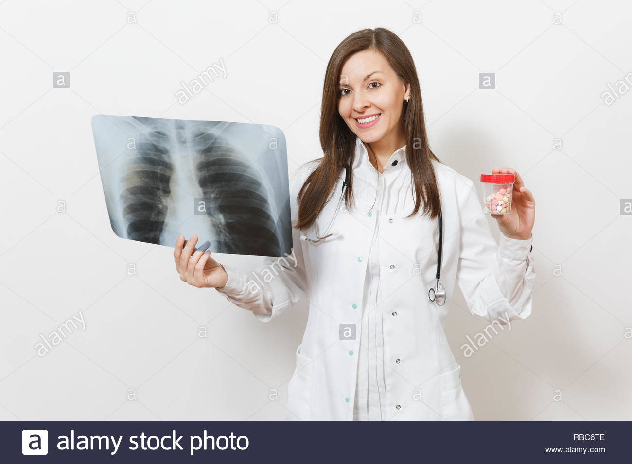 Doctor woman with bottle with pills, X-ray of lungs, fluorography, roentgen isolated on white background. Female doctor in medical gown stethoscope. H - Stock Image