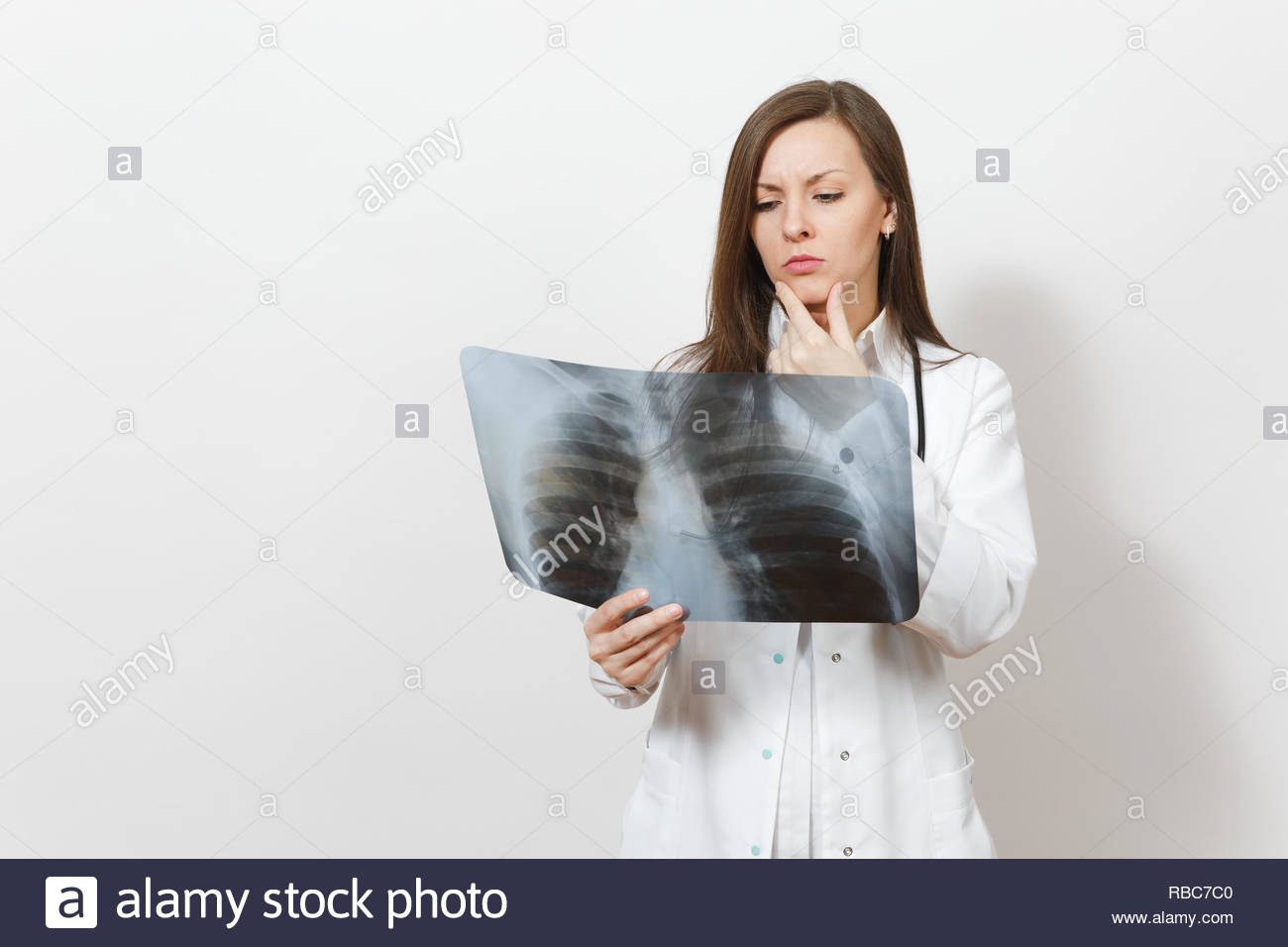Perplexed focused doctor woman with X-ray of lungs, fluorography, roentgen isolated on white background. Female doctor in medical gown stethoscope. He - Stock Image