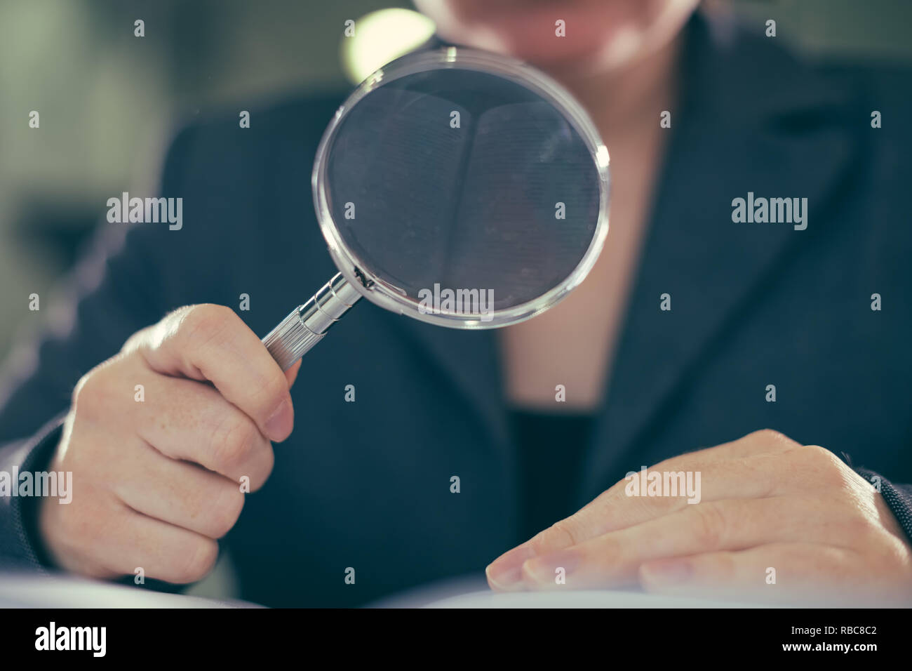 Business corruption audit inspection concept, female inspector using magnifying glass - Stock Image