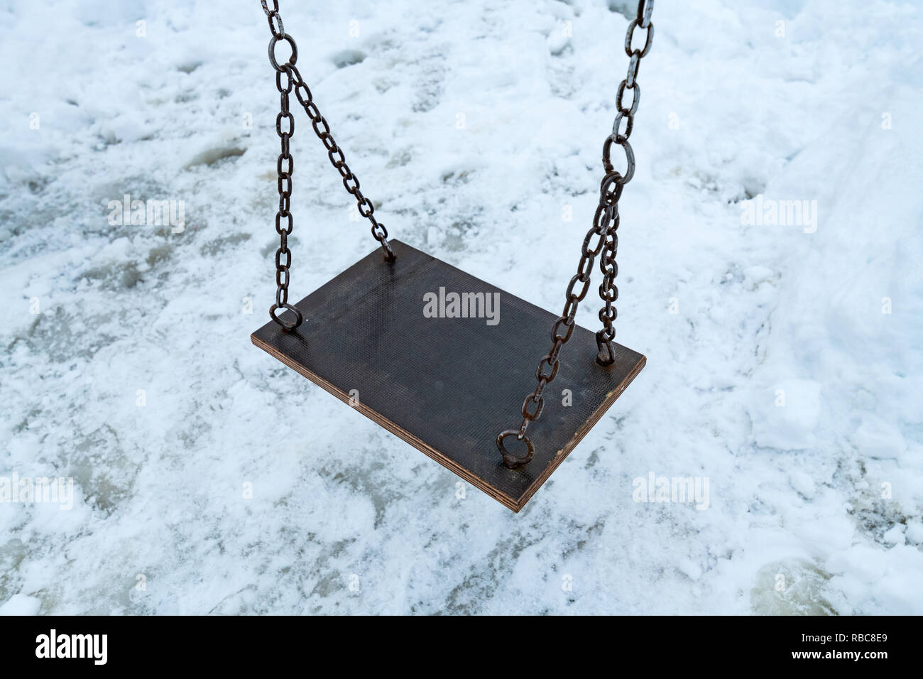 Empty swing in winter with snow covering children's playground - Stock Image