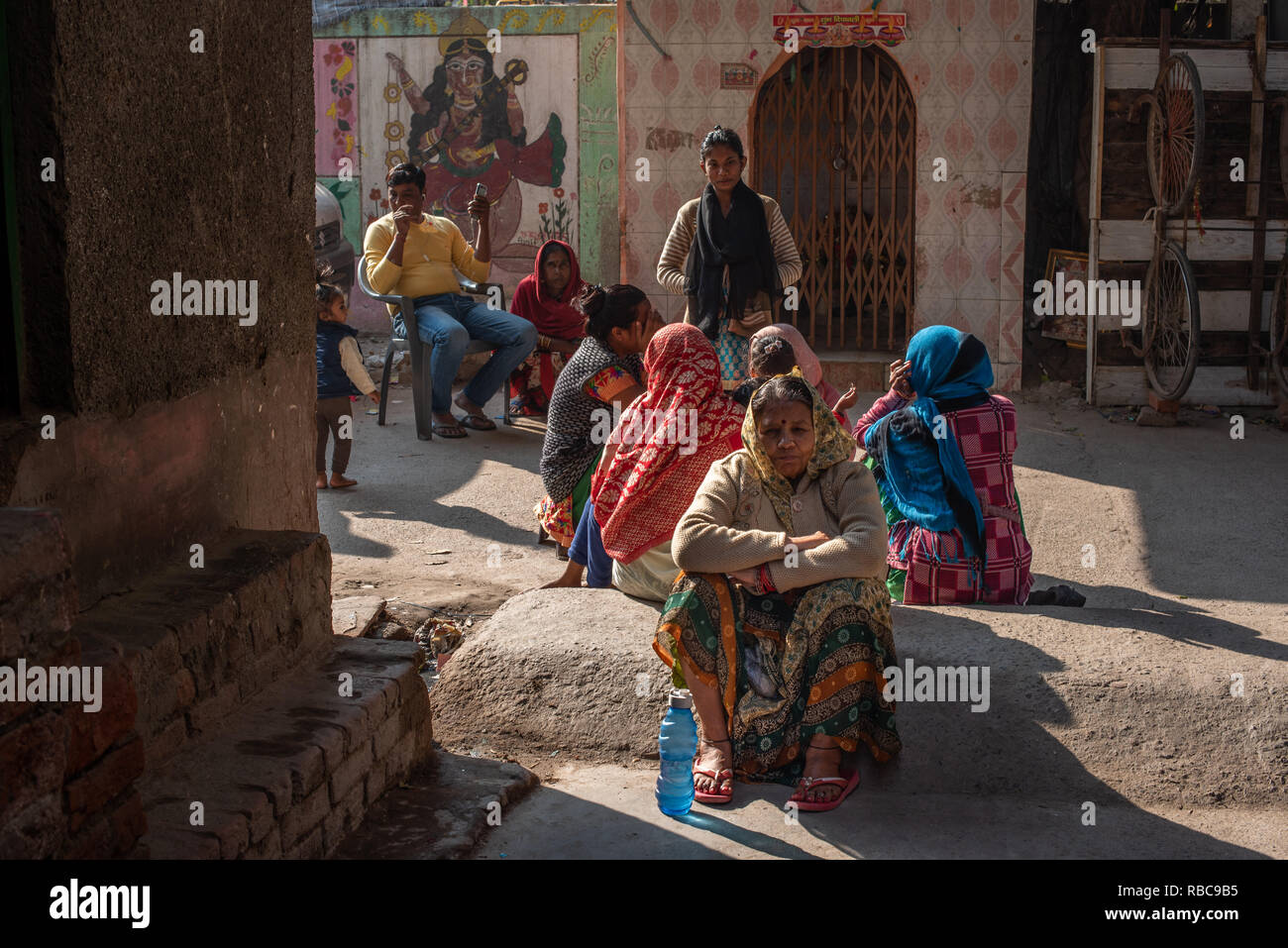 Life on the streets on a wintery sunny afternoon in JJ Colony Madanpur Khadar, New Delhi - women group together sitting in front of a temple. Stock Photo