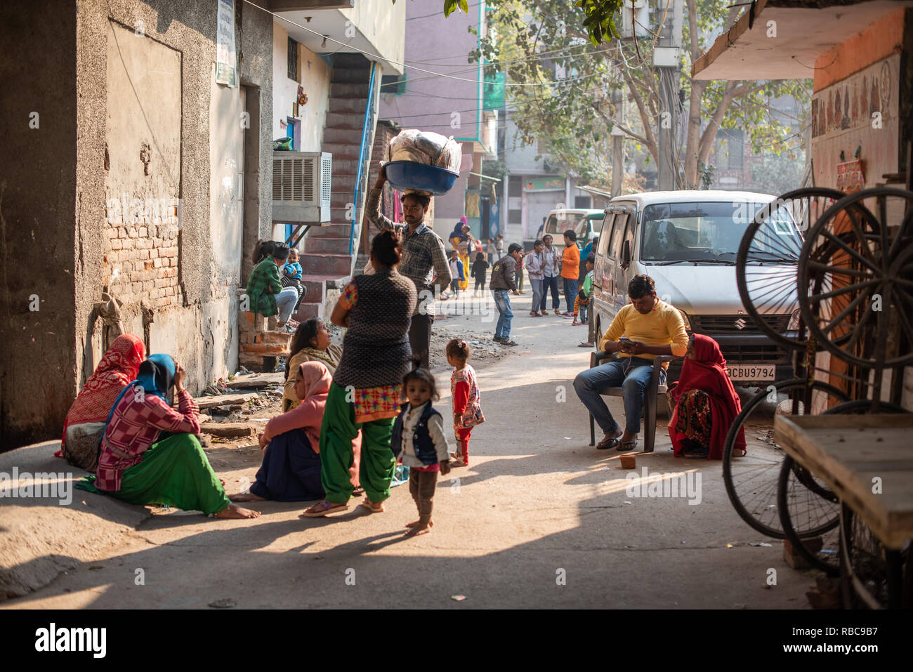 Life on the streets on a wintery sunny afternoon in JJ Colony Madanpur Khadar, New Delhi - people group together approached by a vendor. Stock Photo