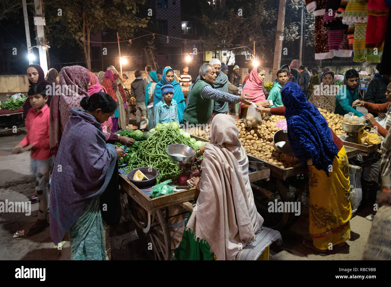 Multiple interactions as shoppers crowd around bustling vegetable market stalls in the night in JJ Colony, Madanpur Khadar, New Delhi, India. - Stock Image