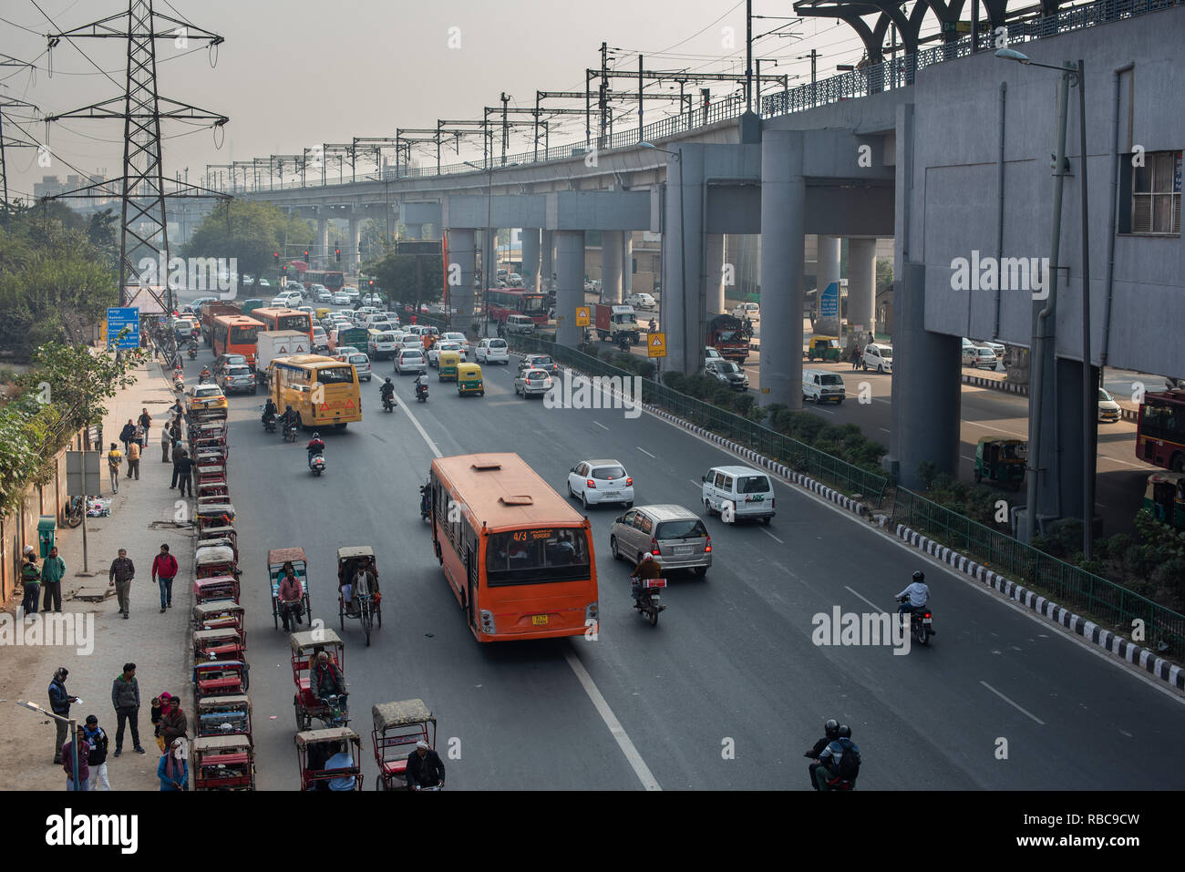View of the travel interchange outside Sarita Vihar Metro station in New Delhi with rickshaws waiting for customers, buses and traffic moving. Stock Photo