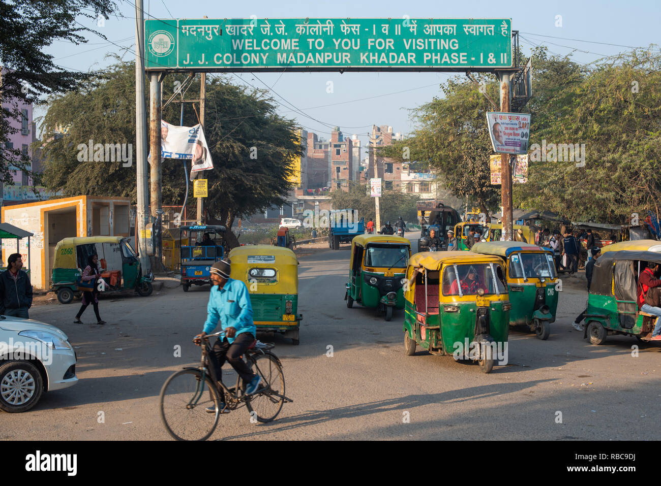 Welcome sign to JJ Colony Madanpur Khadar forms a gateway to the colony framing the entrance road busy with auto-rickshaws and other traffic. New Delhi. Stock Photo