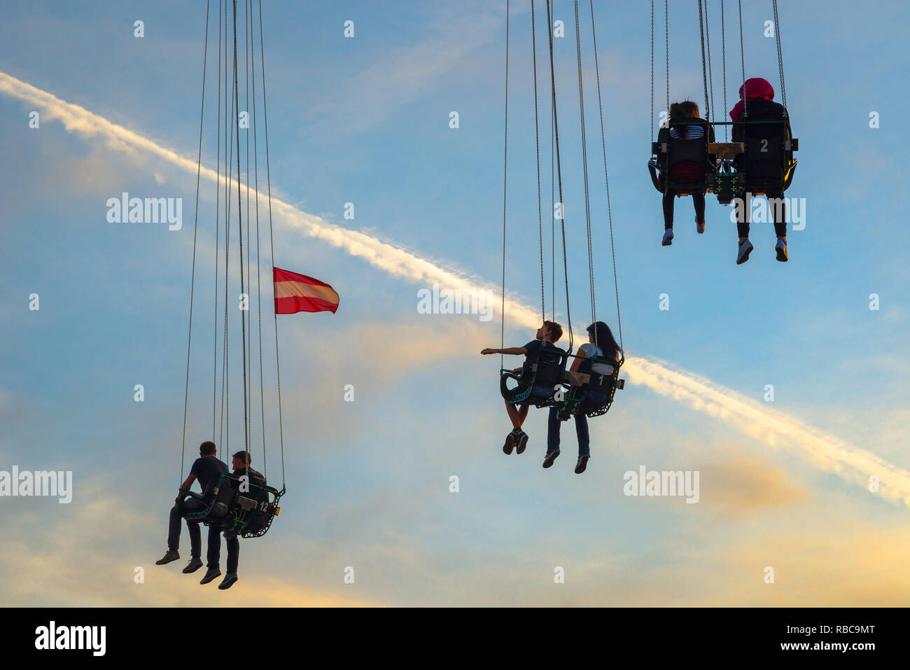 Stranded people waiting, couples suspended in mid-air on the Prater Turm in Vienna's Prater amusement park wait expectantly for the ride to begin. - Stock Image