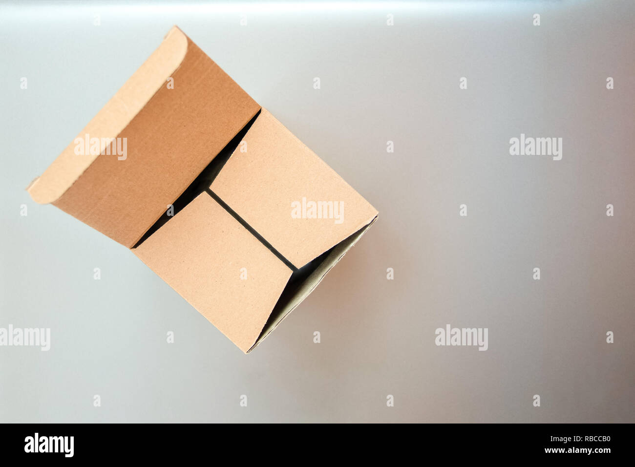 Half closed, half opened big square cardboard craft gift box on the silver gray metal background - Stock Image