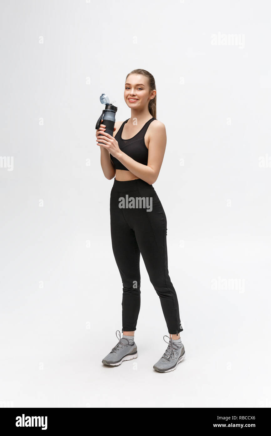 Side view full length portrait of a young healthy sports woman holding a water bottle isolated on a white background - Stock Image